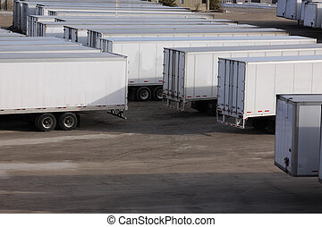 A parking lot with lots of transport trucks and trailers.