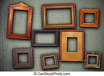 lots of picture frames hung on green wall - lots of empty...