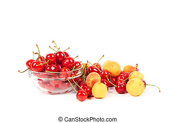 Lots of ripe fresh apricots and cherries in a glass vase isolated on white background