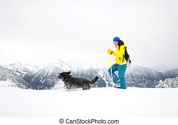 Lots of snow during an excursion with snowshoes. A girl with her beloved dog