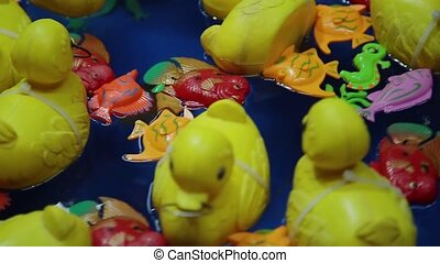 Lots of toy ducks floating on the water. The yellow colored duck toys are very cute.