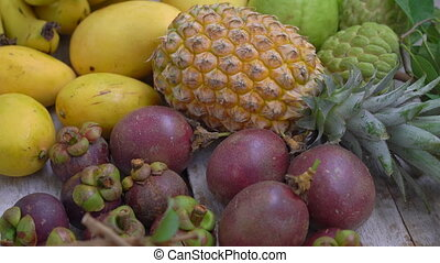 Lots of tropical fruits on a wooden background.
