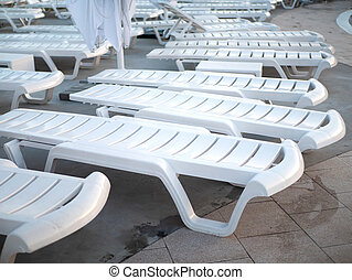 Lots of white empty sun loungers at the pool closeup at sunset