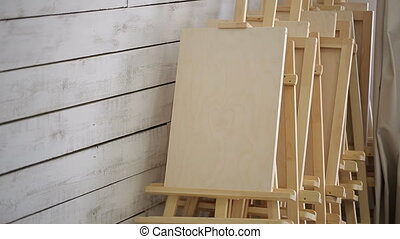 Lots of wooden easels stand in corner of workshop. They are...