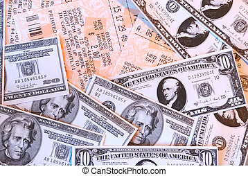 Macro background of lottery tickets and cash winnings in tens and twenties US currency.