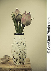 lotus flowers in vase on wooden table over wall grunge background, vintage style
