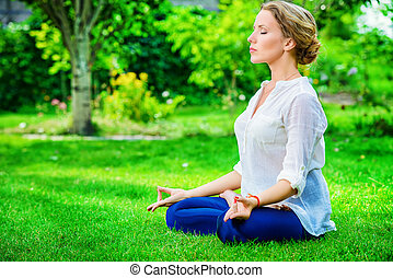 lotus pose - Beautiful young woman doing yoga in the summer...