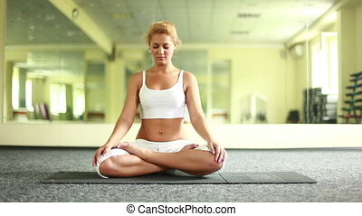 Lotus position. Young adult smiles.