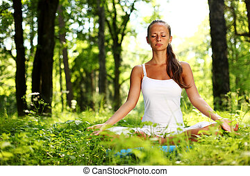 lotus yoga sunrise - yoga woman on green grass in forest