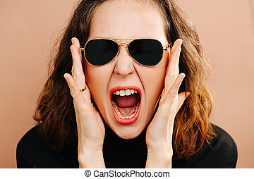 Loud shout portrait of a girl in dark glasses close-up