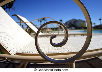 Lounge Chairs - A line of lounge chairs near a pool in...