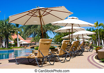 Lounge chairs by poolside in Thailand .