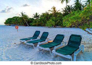 Lounge chairs on a beautiful tropical beach at Maldives