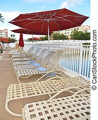 Lounge chairs and umbrellas set up by a resort swimming pool...
