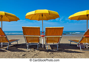 Lounge chairs under a yellow umbrella - Empty lounge chairs...