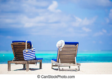 Lounge chairs with bag and hat on tropical beach at Maldives...