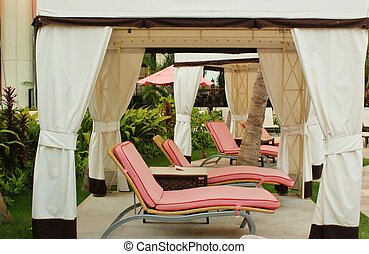 Lounge chairs with pink cushions in a luxiorious cabana