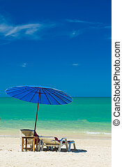 lounge chairs with sun umbrella on a beach