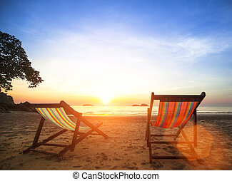 Loungers on deserted coast sea at sunrise.