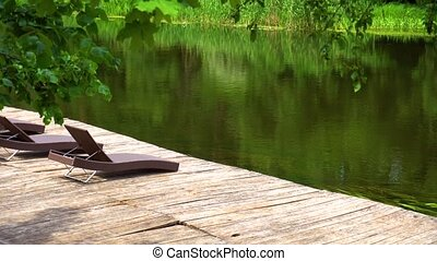 Loungers on the wooden pier on river without people -...