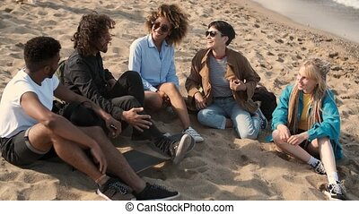 Lounging happy friends on beach - Smiling young multiethnic...