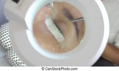 Loupe close-up of professional master make long lashes holding out a pair of tweezers. Eyelash extension in beauty studio.