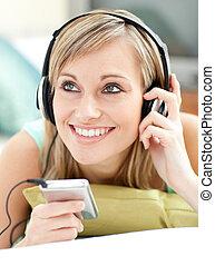 loura, mulher jovem, escutar, música, mentindo, ligado, um, sofá
