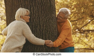 Love and affection at old age. Older couple having romantic autumn day in forest. Hugging tree and smiling