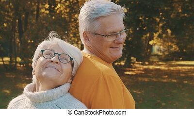 Love and affection at old age. Retired couple enjoying autumn day in forest