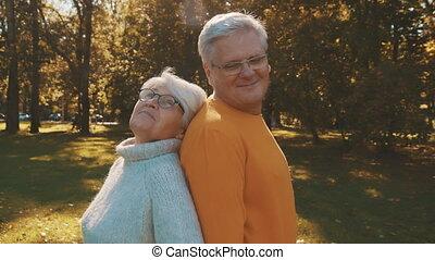 Love and affection at old age. Retired couple enjoying autumn day in forest staying back to back and smiling