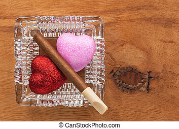 Love and harmful habit in a glass ashtray, conceptual image
