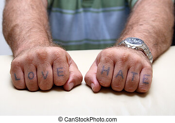 Thug hands with stereotypical love and hate tattooed on fingers