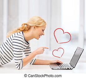 smiling student girl pointing her finger at laptop - love...