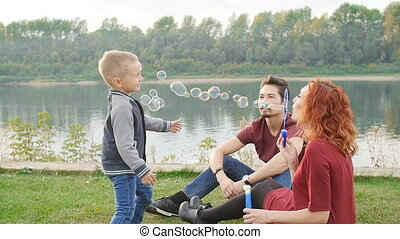 Love and parenthood concept. Happy Family with children blow...