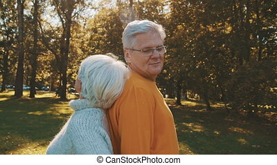 Love and romance at old age. Retired couple enjoying autumn day in forest staying back to back and smiling