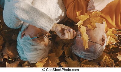 Love and romance in old age Elderly couple lying on the forest ground and playing with yellow autumn leaves.