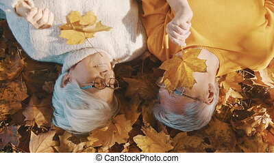 Love and romance in old age happy elderly couple lying on the forest ground and playing with yellow autumn leaves.