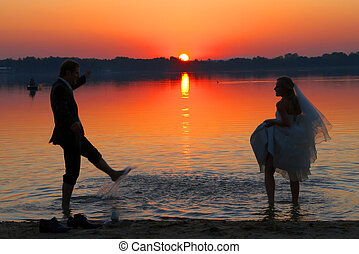 love and sunset - the young couple is standing after the...