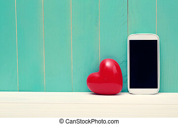Love and technology theme with big red heart and smart phone