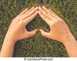 Love and Valentine's Day concept. Retro woman hand in shape of heart on green grass background.