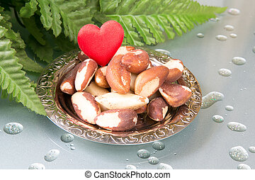 Love Brasil nuts - Brasil nuts on the plate and green leafs