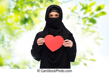muslim woman in hijab holding red heart