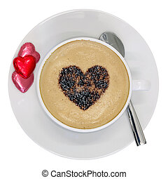 Cup of cappuccino coffee with a love heart sprinkle on top and heart shaped chocolates on the side, isolated on white background with clipping path.