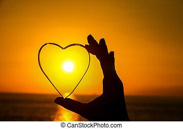 Love Concept Heart and Sun Setting on the Atlantic Ocean