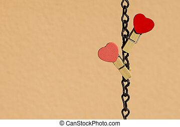 Love concept: Two clips with heart shape on a steel chain