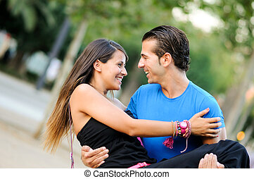 Love couple embracing outdoor in park looking happy