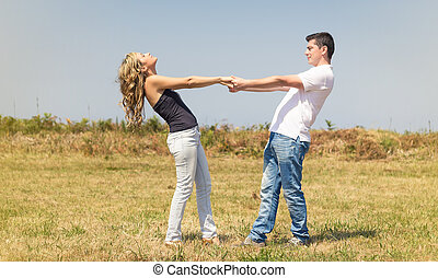 Love couple holding hands outdoors on a summer day