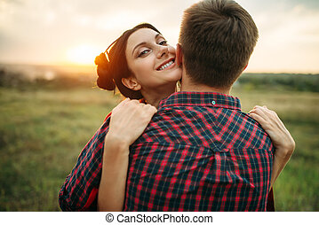 Love couple hugs on the meadow at sunset