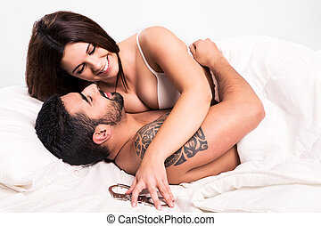 Love couple in bed - Love couple flirting and hugging in bed
