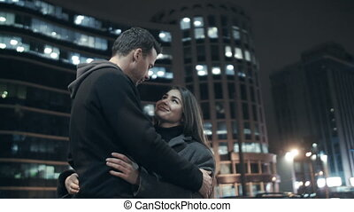 Love couple in town at night embrace.